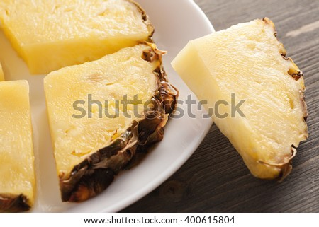 Sliced pineapple pieces on white ceramic plate on wooden table, closeup shot, selective focus, top view - stock photo