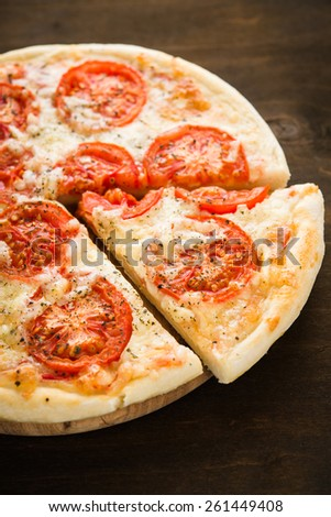 Sliced pizza with tomato, cheese and dry basil on dark wooden background close up. Italian cuisine. - stock photo