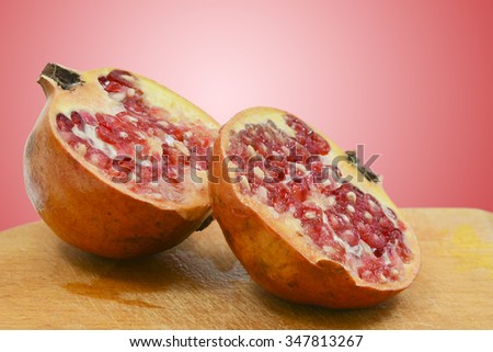 Sliced pomegranate on a wooden plate before red background