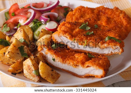 Sliced pork schnitzel, salad and fried potatoes on a plate close-up. horizontal