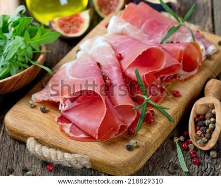 sliced prosciutto on a wooden board - stock photo