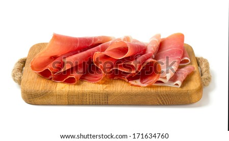 sliced prosciutto on a wooden board isolated on white background