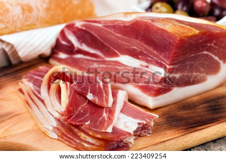 sliced prosciutto on a wooden table - stock photo