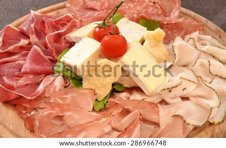 Sliced prosciutto salami and cheese dish. - stock photo