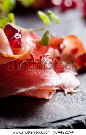 Sliced prosciutto with herbs and pomegranate seeds - stock photo