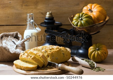 Sliced pumpkin bread in rustic farmhouse setting with old fashioned weighing scales - stock photo