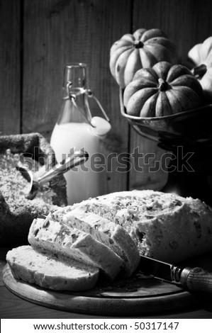 Sliced pumpkin bread in rustic farmhouse setting with old fashioned weighing scales in black and white - stock photo