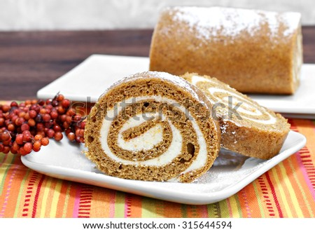Sliced pumpkin roll cake with whole cake in background.  Fall setting and colors with copy space. - stock photo