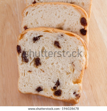 sliced raisin bread on wood background-close up shot