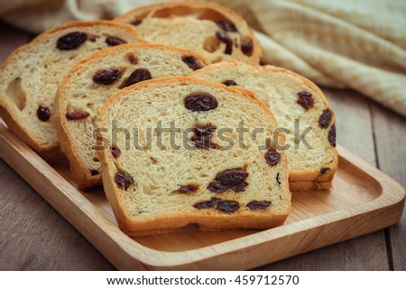 Sliced raisin bread on wooden plate
