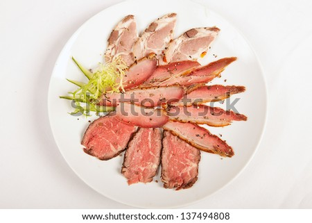 sliced rare beef, roast covered in pepper and herbs - stock photo