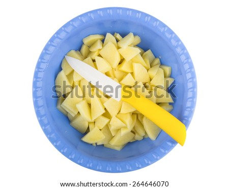 Sliced raw potatoes and knife in plastic bowl isolated on white background. Top view - stock photo