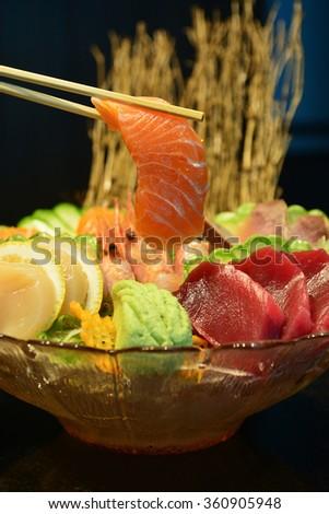 sliced raw salmon with chopsticks holding it on sashimi set - stock photo
