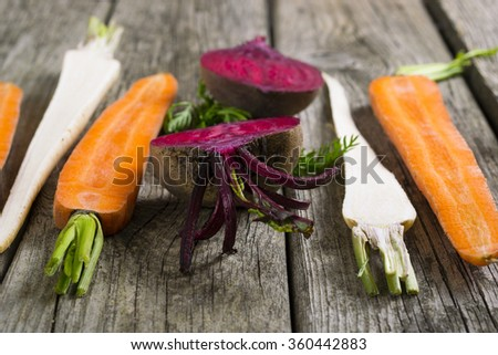 sliced raw vegetables: carrot, turnip, beetroot and parsley on old wooden table background