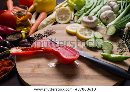 Sliced raw vegetables on a cutting board and a kitchen knife and more raw vegetables and spices around - stock photo