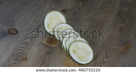 Sliced raw zucchini on wooden