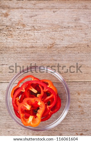 sliced red bell pepper in a bowl on rustic wooden table - stock photo