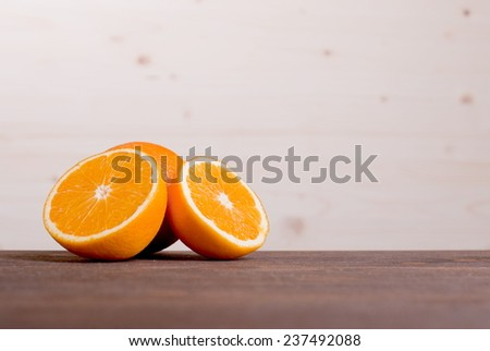 sliced ripe appetizing delicious orange on cutting board brown table - stock photo