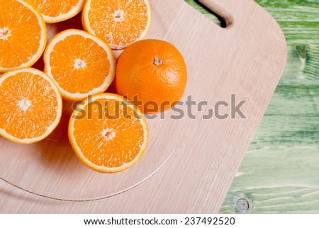 sliced ripe appetizing orange on a cutting board on a green table - stock photo