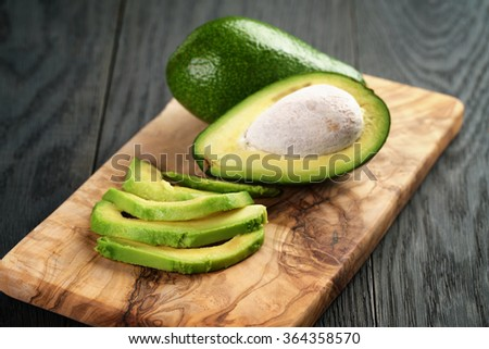 sliced ripe avocados on olive cutting board - stock photo