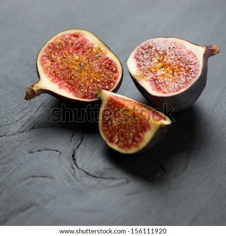 Sliced ripe figs on a black wooden background, studio shot
