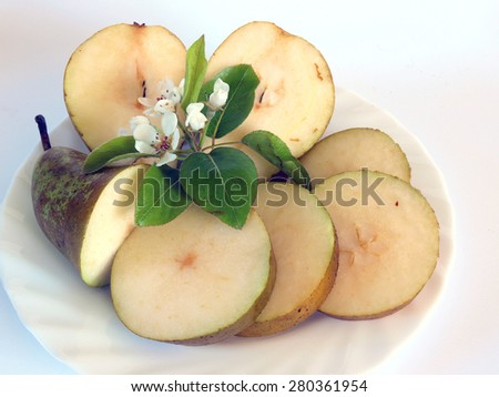 Sliced ripe pears on white dish and white background with blossoms and leaves - stock photo