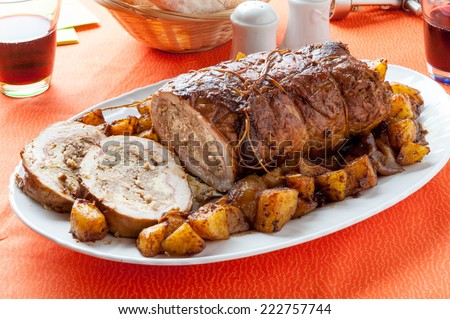 Sliced roasted and stuffed meatloaf with a side of baked potatoes - stock photo