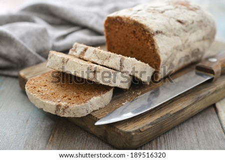 Sliced rye bread on cutting board closeup on wooden background