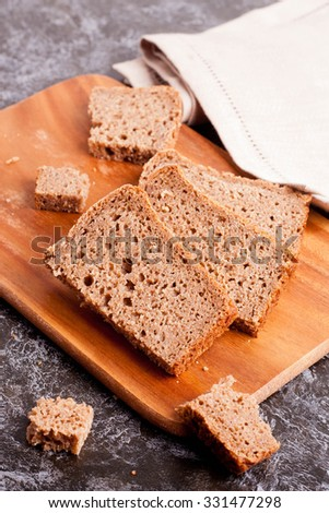 Sliced rye bread on cutting board closeup, top veiw, vertical