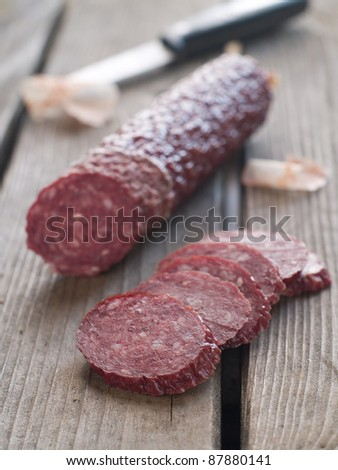 Sliced salami on rustic wooden table, selctive focus - stock photo