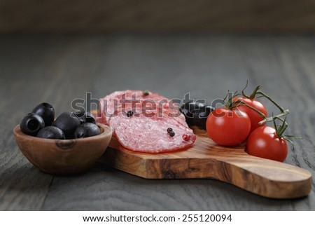 sliced salami with pepper on olive board on table - stock photo