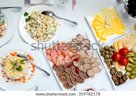 sliced sausages, pickles and salads on a banquet table - stock photo