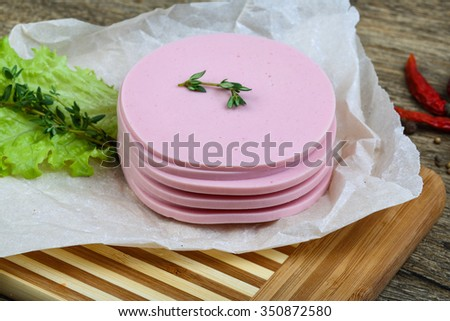 Sliced sausages with salad leaves and thyme on the wood background - stock photo