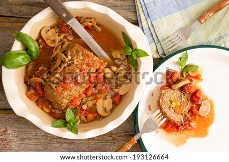Sliced savory meatloaf with mushrooms and vegetables served in a casserole on a rustic wooden table with grungy peeling red paint, overhead view, copy space on the left - stock photo