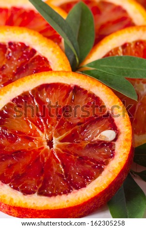 Sliced Sicilian blood red orange with leaf close up. - stock photo