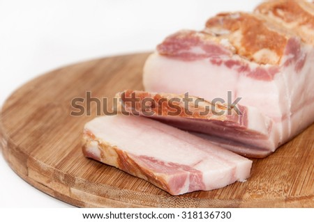 Sliced smoked bacon on the wooden board. - stock photo