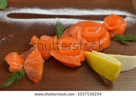 Sliced Smoked or Salty fresh Salmon with Lemon and Dill selective focus. restaurant food. Fish dish, banquet, catering served plate at rustic wood with vegetables at background.