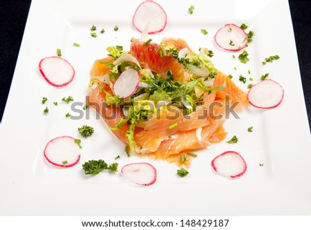 sliced smoked salmon salad with blood orange and radish. seafood appetizer