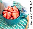 Sliced strawberries in a bowl with cup of milk, white sugar and wooden spoon - stock photo