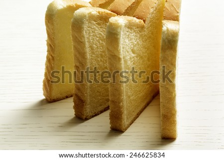 Sliced toast bread shown on a surface of white table - stock photo