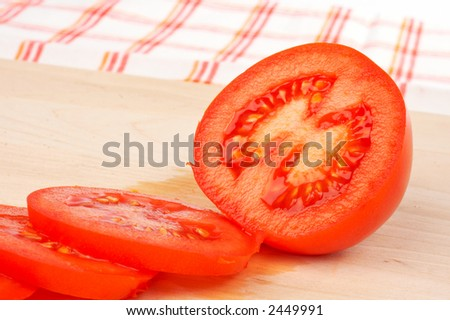 Sliced tomatoes with shadow on wood background - stock photo