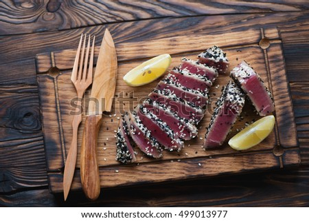 Sliced tuna steak roasted with sesame seeds on a wooden tray, top view