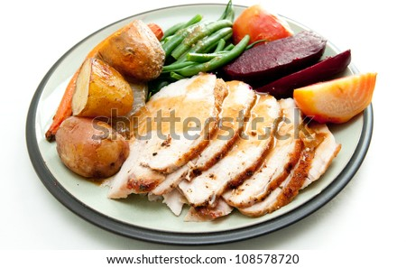 sliced turkey with roasted potatoes, fresh string beans and sugar beets, plus some sweet potatoes - stock photo
