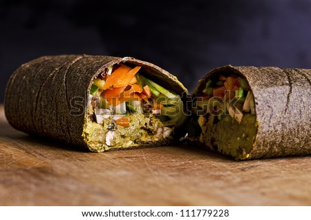 sliced up raw food wrap with vegan ingredients and green pesto on a wooden plate - stock photo