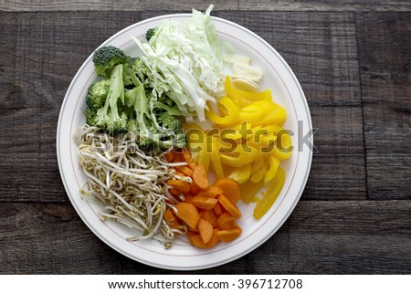Sliced vegetables placed on the white plate. - stock photo