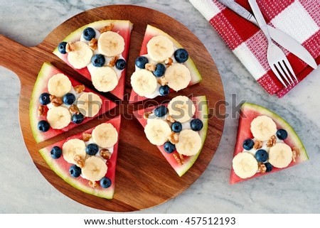 Sliced watermelon pizza with bananas, blueberries, nuts and yogurt, above view on serving board