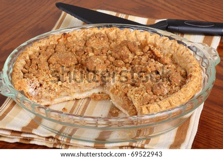 Sliced whole apple crumb pie in a pie dish - stock photo