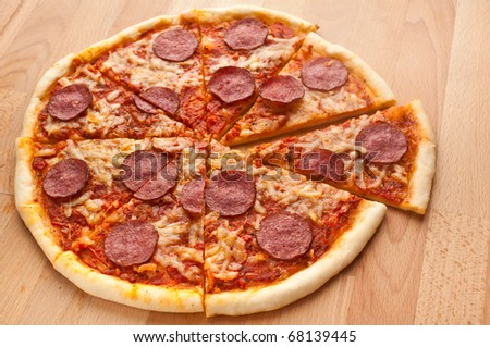 sliced whole salami pizza on a wooden table - stock photo