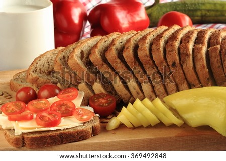 Sliced whole wheat bread with tomatoes, butter, paprika and a mug - stock photo