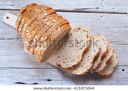 Sliced wholegrain bread on a wooden cutting board. - stock photo